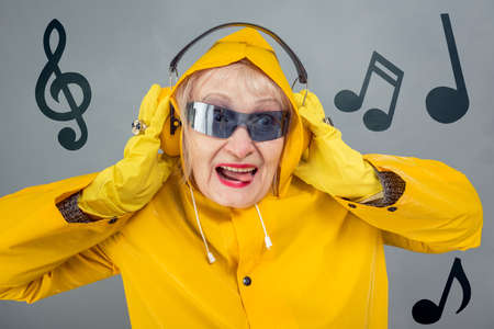 A fashionable elderly lady in yellow is listening to music with headphones. The concept of a party, a disco, a young state of mind. Close-up on a gray background.