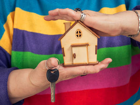 Hand holding a house with a house key Banque d'images