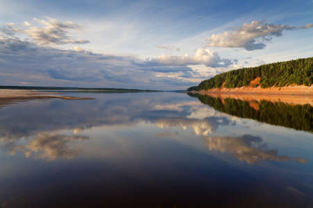 placid water: the reflection of the shoreline of the river