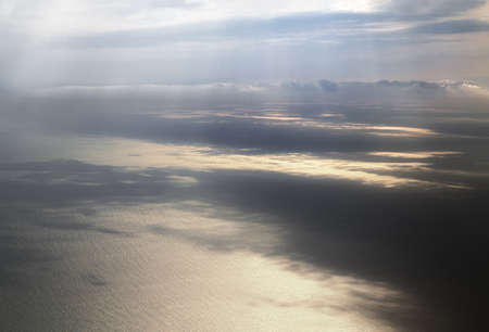 suns rays illuminate the surface of the sea through the clouds