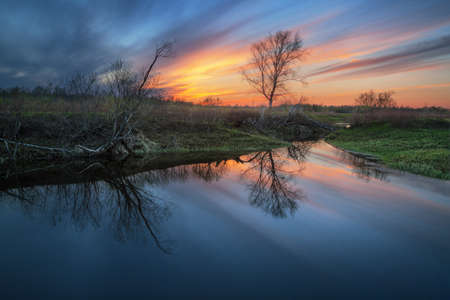 reflection of a beautiful sunset in a spring pond