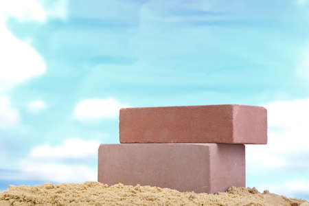 Two pink ceramic bricks on the sand at the blue sky background