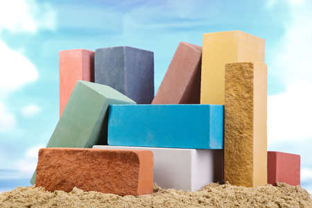 Set of multi-colored ceramic bricks on the sand at the blue sky background 스톡 콘텐츠