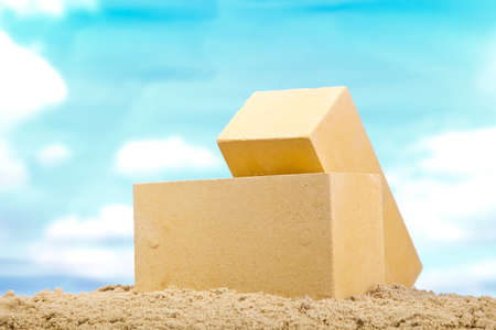 Two yellow ceramic bricks on the sand at the blue sky background