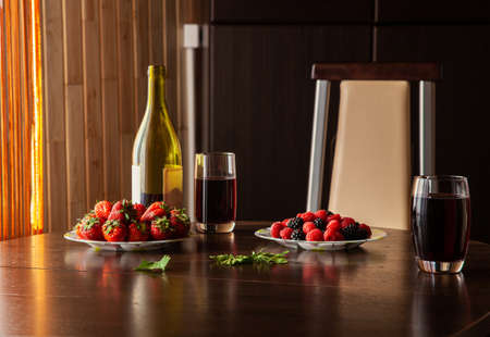Strawberry with raspberry and red wine nature morte at the table