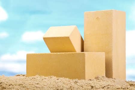 Three yellow ceramic bricks on the sand at the blue sky background