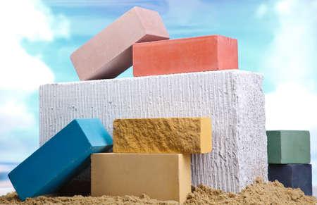 Set of multi-colored ceramic bricks on the sand at the blue sky background Banco de Imagens