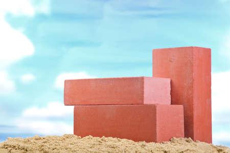 Three red ceramic bricks on the sand at the blue sky background 스톡 콘텐츠