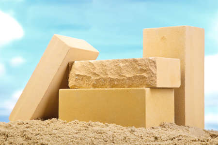 Four yellow ceramic bricks on the sand at the blue sky background 스톡 콘텐츠