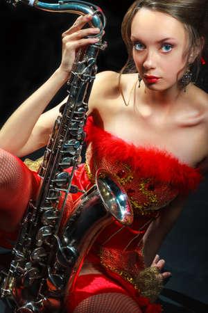 Frau im roten Kleid mit Saxophon auf schwarzem Hintergrund