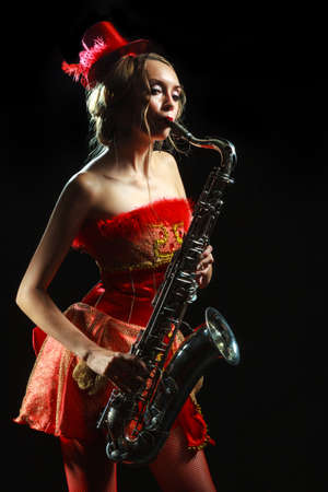 Woman in red dress with saxophone at the black background