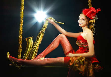 Woman in red dress with saxophone at the swing at the black background