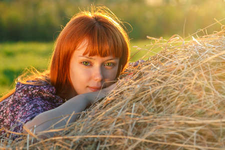 Portrate of young beautiful woman with red hair on the haystack in motning sunlight