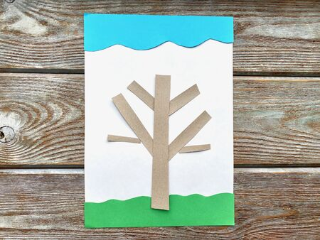 3D applique of colored paper, volume, spring tree with flowers, on a wooden background, handmade. 写真素材