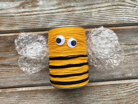 A bee made of yarn and a tin can without a mustache, childrens creativity.