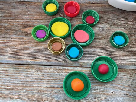 plastic lids with plasticine, childrens needlework, on a wooden background. Stock Photo