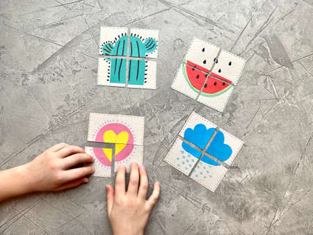 Childrens hands put together a puzzle, a logical, interesting game.,
