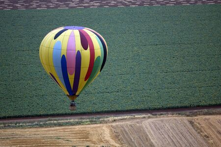 A hot air balloon above fields landscape photo