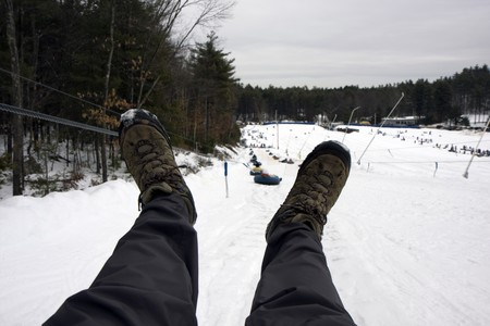 Snow tubes lift to the top of the mountain with legs of the rider