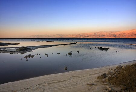 The water of the dead sea with the Jordan mountains and salt sculptures at sunset photo
