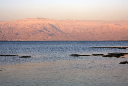 The water of the dead sea with the Jordan mountains and salty islands at sunset