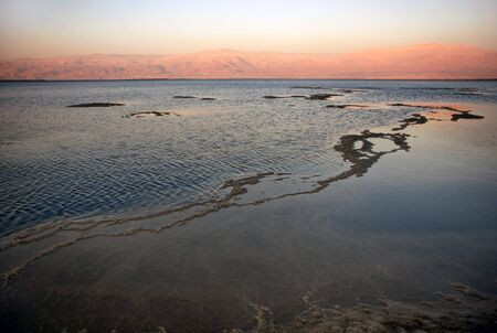 The water of the dead sea with the Jordan mountains at sunset