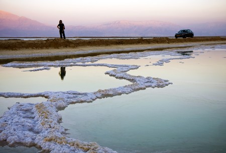rock bottom: The water of the dead sea with salty paths at sunset and a person and a car