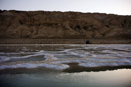The water of the dead sea with salty paths at sunset photo