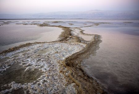 The water of the dead sea with salty paths at sunset