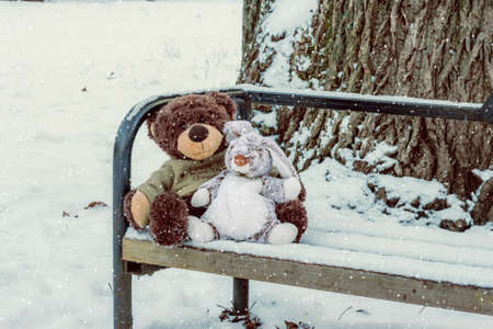 pedagogical: Toy bear and a hare sitting on the bench in the snow Stock Photo