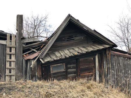 An old rickety wooden hut with boarded-up windows. There is dry grass and trees all around. The house is falling apart from old age, the boards are darkened.