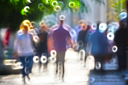 transience: Blurred silhouettes of people walking on the street against backlight
