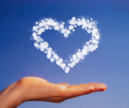 endear: A hand holding a heart as a sign of love and affection  A light blue sky is a background