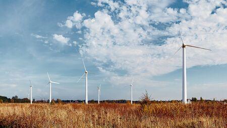 Wiatraki na polu z niebieskim niebem. Energia alternatywna.