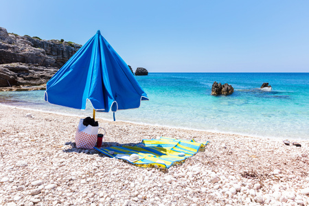 Folded umbrella with bag and bedding on the beach Banco de Imagens