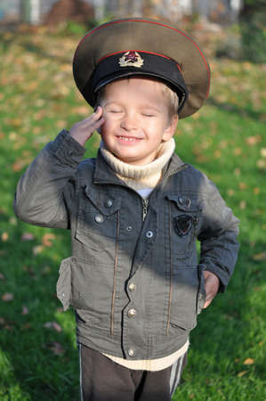 Boy playing soldier wearing Soviet military cap his grandfather photo