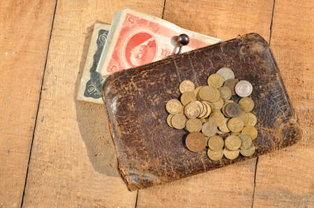 change purses: Vintage leather purse with a handful of coins and banknotes on the background of wooden boards