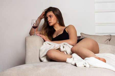 brooding woman with a glass of wine on the bed sadness wants love