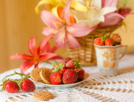 beautiful still life with a basket of lilies and strawberries photo