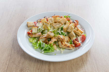 Caesar salad with chicken on wooden table