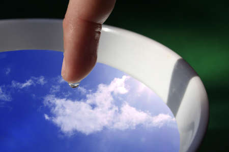 bowel movement: ringer entering bowl with sky reflection in water droplet on finger Stock Photo