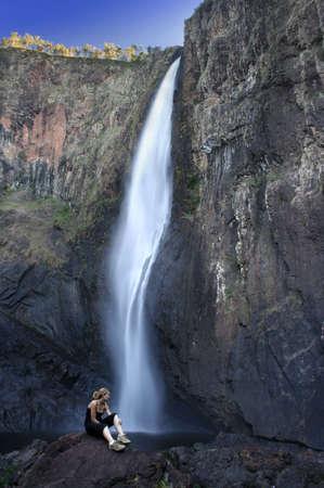 waterfall with sky: woman at base of beautiful waterfall Stock Photo