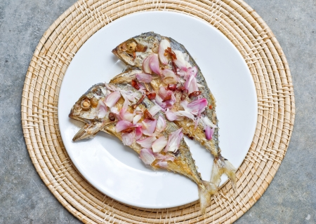 deep fry two mackerel fish topping with sliced shallot and chilli on white plate photo