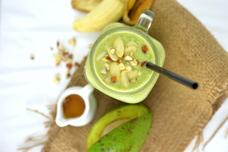 juices: top view of isolated homemade avocado, banana and honey milkshake