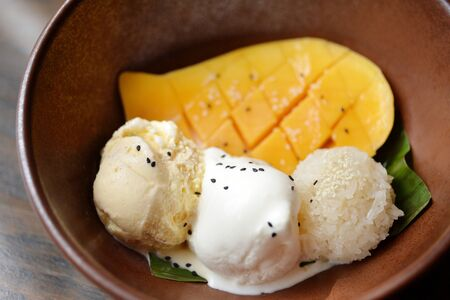 thai dessert: Selective focus of mango ice cream and vanilla ice cream with mango flesh and sticky rice Stock Photo