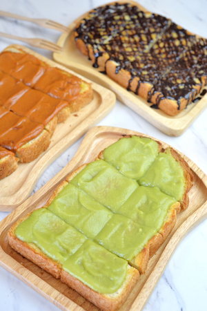 custard slice: Selective focus of Toast with egg custard Kaya cream, milk tea custard and chocolate on top