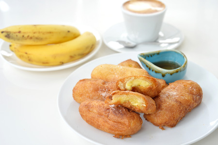 deep fry: Selective focus of deep fry banana with honey syrup and coffee cup