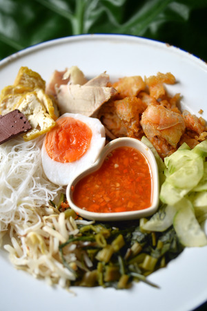 chili sauce: Thai salad with rice noodle, fresh vegetable, tofu, pork, crispy fry shrimp, egg and spicy sauce on banana leaf