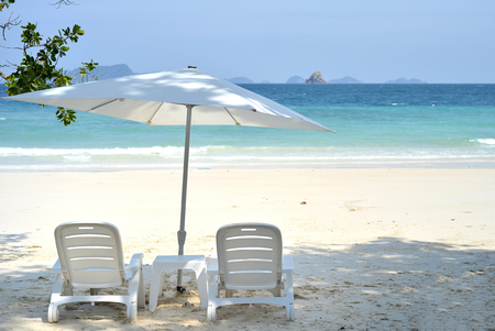 sun umbrella: Two beach chairs with sun umbrella on beach