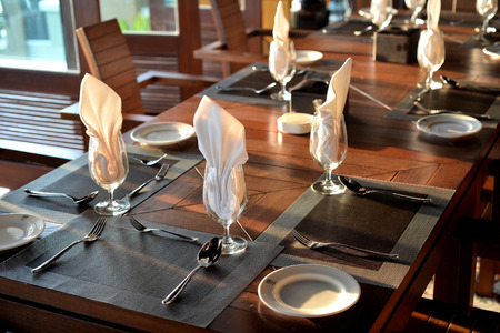 dinner table: Empty glass with napkin and silverware on table for dinner setting